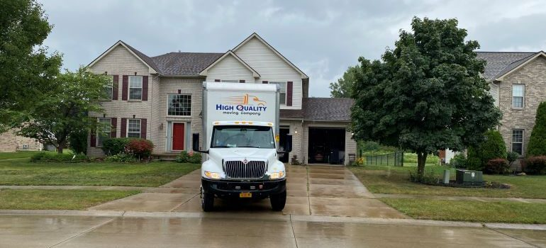 High Quality Moving Company truck in front of a house.