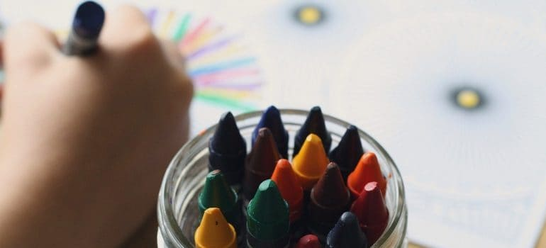 Child making colorful image with crayons.