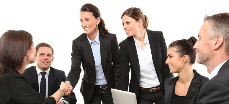 Businesswoman shaking hands - recognize high quality moving companies