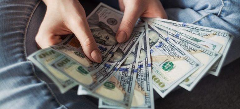 Person holding $100 bills