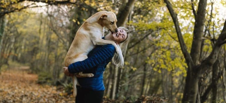 Woman in blue holding a dog in her arms.