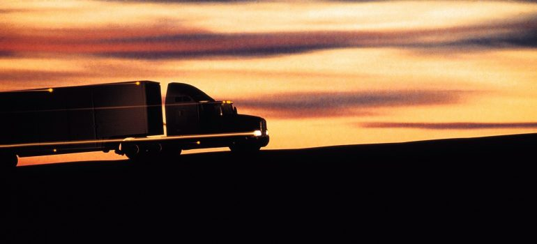 a silhouetter of a truck on the road