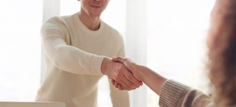 a team member of movers Belleville MI and a woman shaking hands