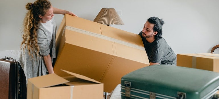 Man and woman carrying a box when moving