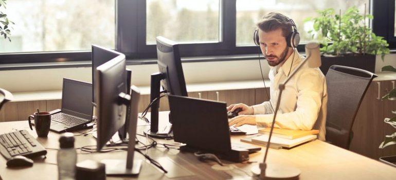 man-with-headphones-facing-computer-monitor