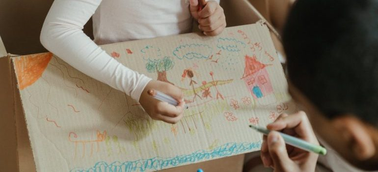 A father and daughter drawing on a moving box.
