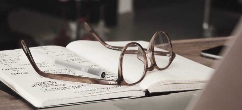 A notebook and glasses.