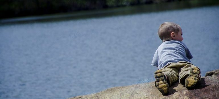 A kid laying on the bank of a lake