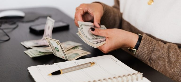 Picture of a woman counting dollars. Prepare your moving budget before moving to Southfield MI