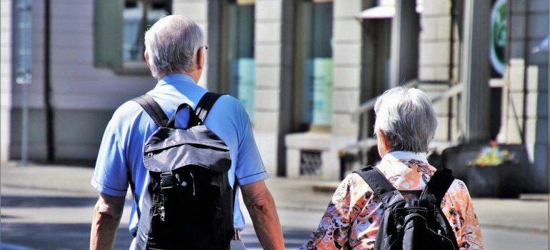 Two elderly people walking on a street