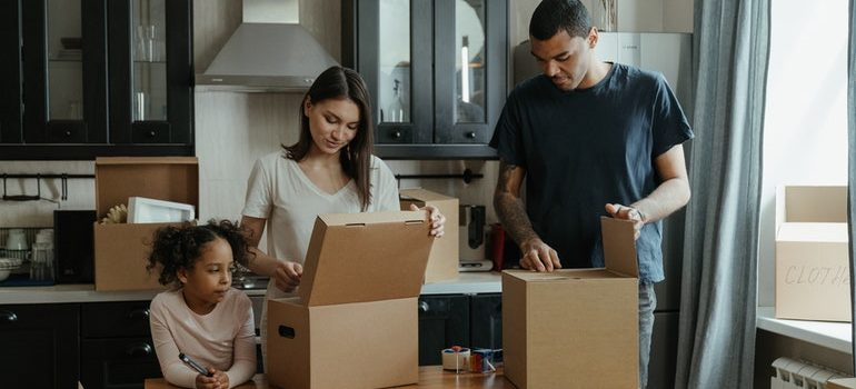 A family packing items in cardboard boxes.