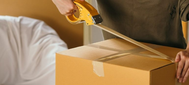 A man taping up a cardboard box before hiring the best movers in Westland MI.