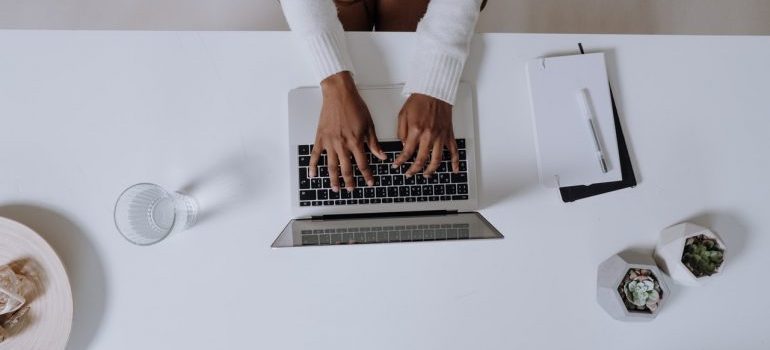 A person typing something on a white laptop.