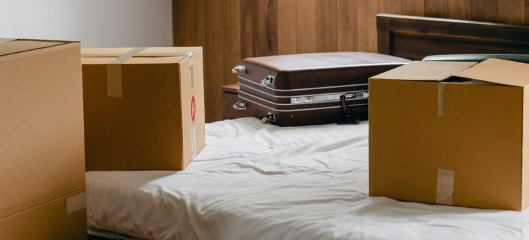 A bed with a cardboard box and a suitcase on it.