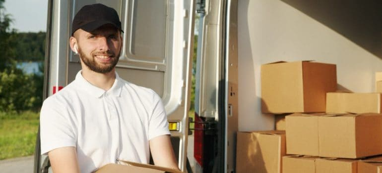 A smiling movers holding a box.