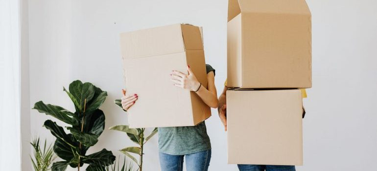 A couple with cardboard boxes.