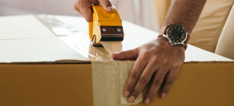 A professional packer closing a moving box.