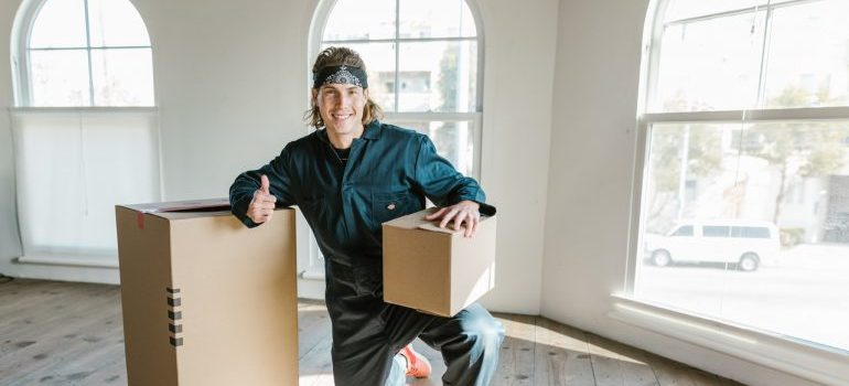 A mover kneeling and holding amoving box.