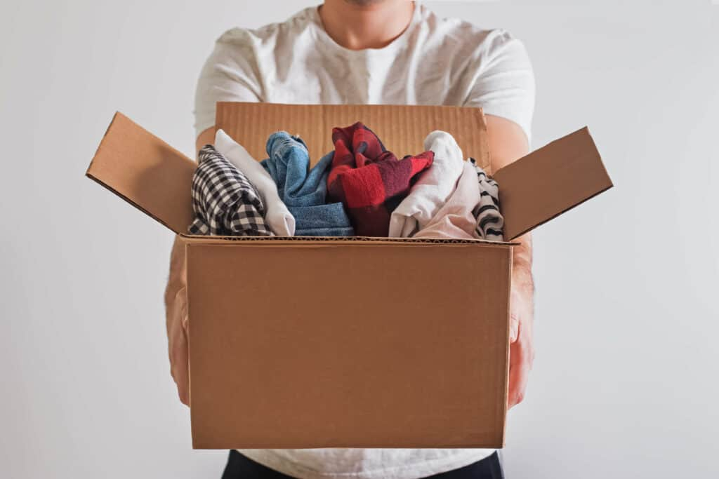 Close-up shot of man's hands holding a box with clothes